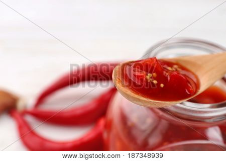 Jar and spoon with tasty chili sauce, closeup