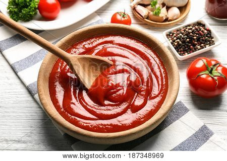 Delicious ketchup in bowl with ingredients on wooden background
