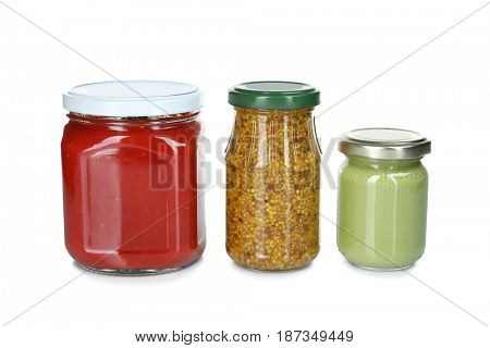 Glass jars of different sauces isolated on white