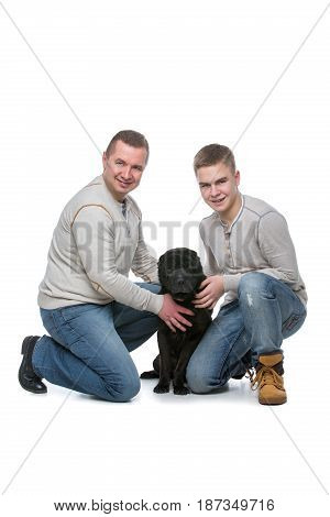Father and son sitting with black shar pei dog. Studio shot isolated on white background. Copy space.
