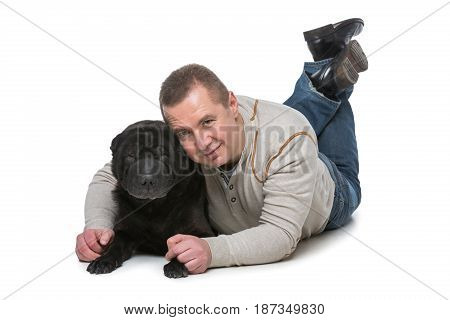 Handsome man hugging black shar pei dog. Studio shot isolated on white background. Copy space.