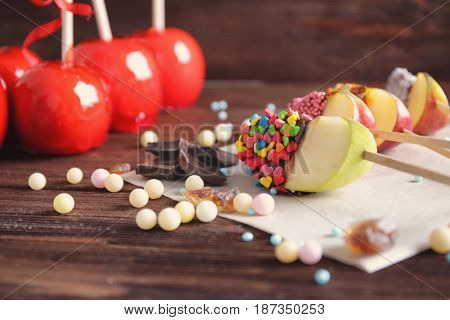 Toffee apples and candied wedges on wooden background