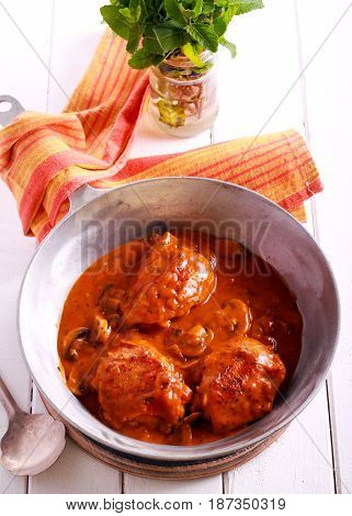 Chicken Valencia - chicken thighs stewed with wine and tomato with mushrooms in a pan