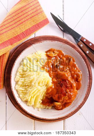 Chicken stew with gravy and mashed potatoes on plate