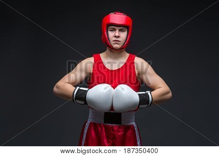 Teenage boxer in red form and white boxing gloves. Studio shot on black background.