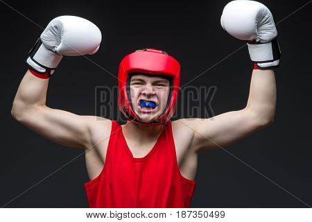 Teenage boxer in red form and white boxing gloves with hands up. Young champion. Studio shot on black background.