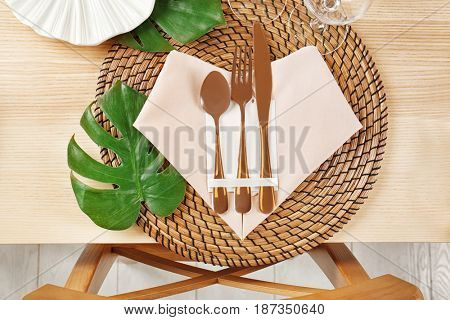 Table setting with pink color napkin and floral decor on wooden surface
