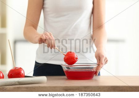 Woman holding candy apple on stick above glass bowl with caramel