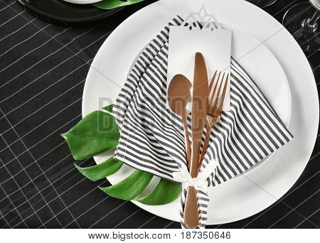 Table setting with striped napkin and floral decor on dark tablecloth