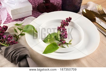 Table setting in lilac color and floral decor on white tablecloth