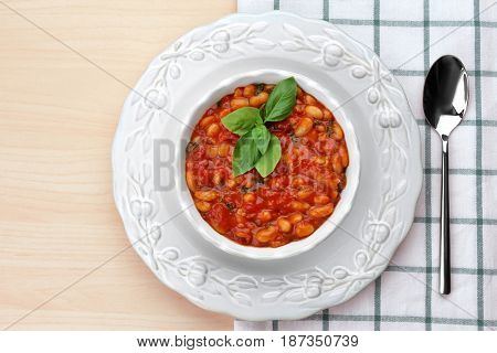 Beautiful dinnerware with delicious Italian butter beans, spoon and napkin on light wooden background