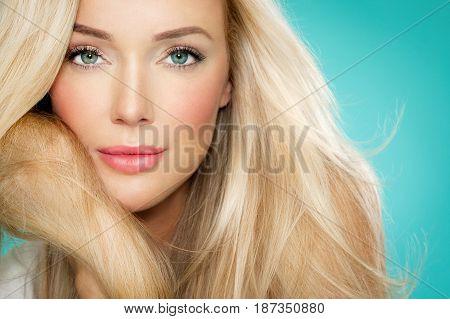 Beautiful blond woman closeup on blue background.