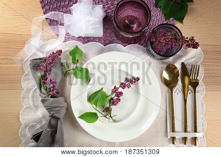 Table setting in lilac color and floral decor on wooden surface