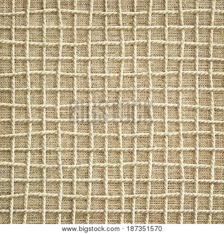 Background of intertwined rope in the form of a grid on canvas