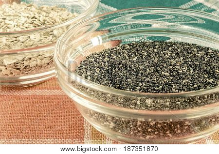 Oat flakes and chia seeds in a glass bowl on colorful dishcloth. Closeup shot. Healthy food concept. Toned.