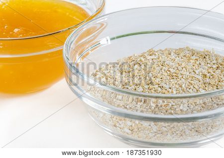 Oat bran and honey in a glass bowl isolated on white background. Closeup shot. Healthy food concept.