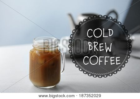 Glass jar of cold brewed coffee with milk on wooden table