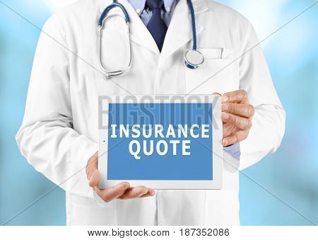 Insurance quote concept. Doctor holding tablet with text on screen against blurred background