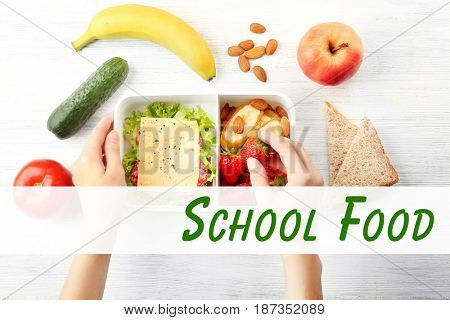 Concept of school lunch. Mother putting food in lunchbox on table