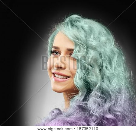 Trendy ideas. Young woman with mint color accent in hairstyle on dark background