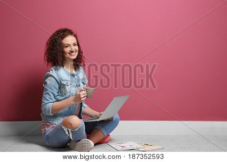 Beautiful young woman using laptop on color wall background