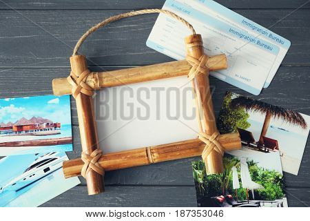 Travel concept. Bamboo frame with space for text, beautiful pictures and arrival cards on wooden background
