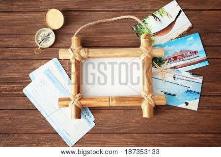 Travel concept. Bamboo frame with space for text, arrival cards and compass on wooden background