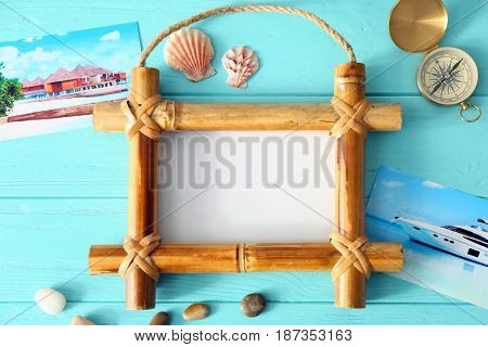 Travel concept. Bamboo frame with space for text, compass, and cute decorations on wooden background