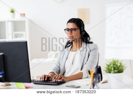 communication, business, people and technology concept - smiling businesswoman or helpline operator with headset and computer typing at office