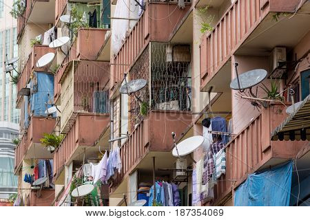 Kuala Lumpur 09/09/2016 Old apartment building balconies with washing out drying and many satellite dishes.