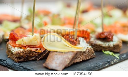 Bruschetta with cheese and sun-dried tomatoes on a stone plate