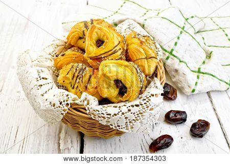 Cookies with dates in a wicker basket with a napkin, fruit and towel on a background of wooden boards