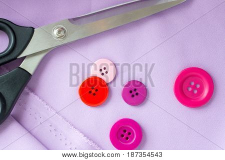needlework and tailoring concept - scissors, sewing buttons and cloth