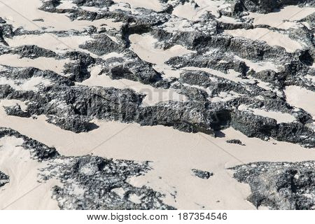 background and texture concept - close up of stone or volcanic rock surface with sand