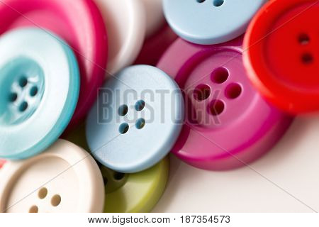 needlework and tailoring concept - sewing buttons