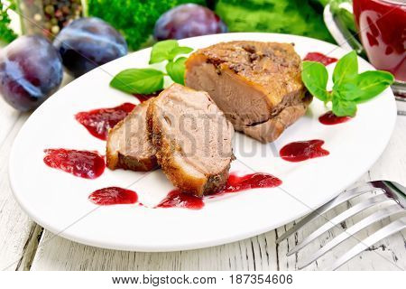 Duck breast with basil and plum sauce in a white oval plate against a light wooden board