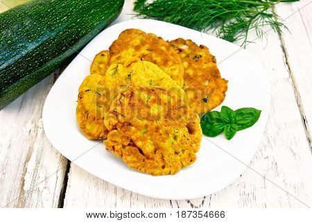 Indian chick-pea flour flatbreads with zucchini and fresh herbs, basil in a plate on a wooden boards background
