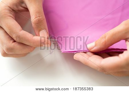 people, needlework, sewing and tailoring concept - tailor woman with thread in needle stitching fabric pieces together