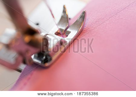 needlework and tailoring concept - sewing machine presser foot stitching fabric