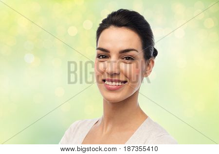 dental, portrait and people concept - happy smiling young woman with braces over green background and lights