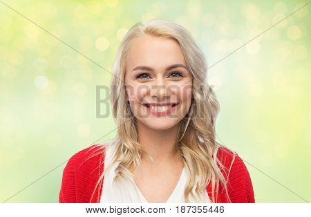 fashion, portrait and people concept - happy smiling young woman in red cardigan over green background with lights