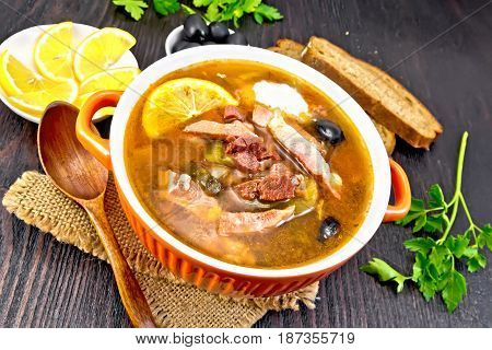 Soup saltwort with lemon, meat, pickles, tomato sauce and olives in a bowl on a sacking, bread on a background of a dark wooden board