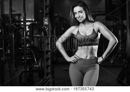 Sexy portrait model and a slim tanned woman's body looking away in fitness gym