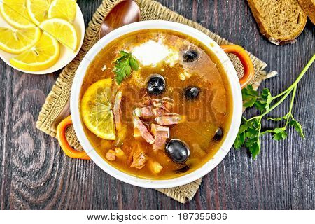 Soup saltwort with lemon, meat, pickles, tomato sauce olives in a bowl on a sacking, bread on a background of a dark wooden board from above