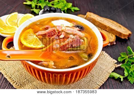 Soup saltwort with lemon, meat, pickles, tomato sauce olives, spoon in a bowl on a sacking, bread on a wooden board background