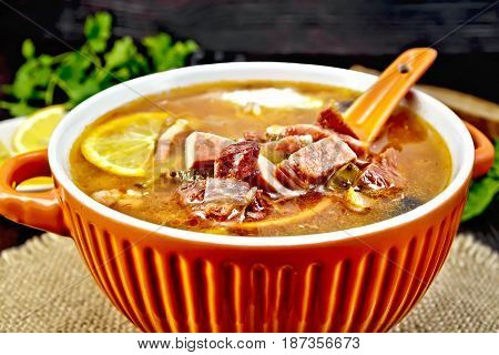 Soup saltwort with lemon, meat, pickles, tomato sauce olives, spoon in a bowl on a sacking, bread on a background of a dark wooden board