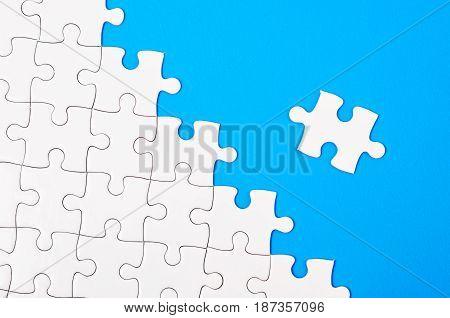 Close up White jigsaw puzzle on blue background.