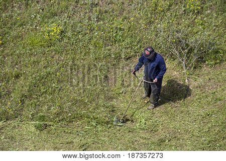 Adult man working with a lawn mower trimmer
