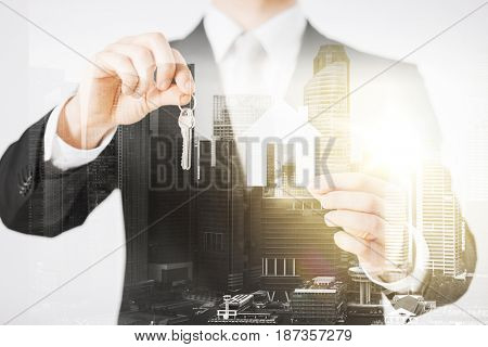 business, people and mortgage concept - close up of businessman holding keys and paper house over city with double exposure