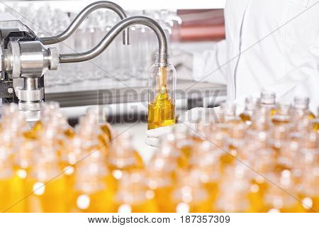 Professional Scientist In White Gown Standing Against Factory Background With Many Glass Bottles Fil